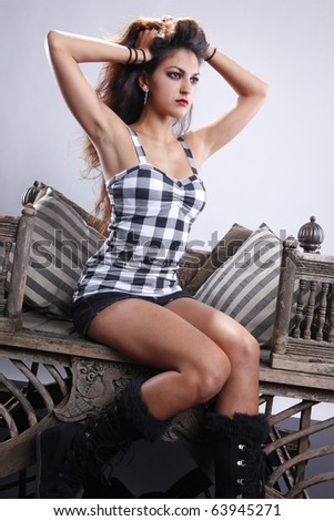 Young brunette in plaid on vintage chair