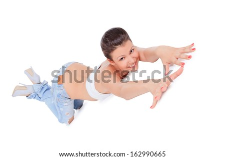 young brunette in ragged jeans posing on the floor - stock photo