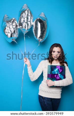 Young brunette in white sweater holds three silver balloon and gift box on a colored background.