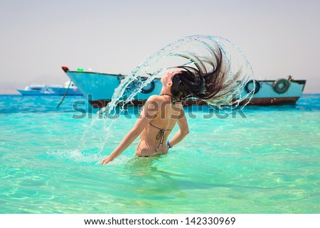 Young brunette jumping out of turquoise water of Red Sea, Egypt - stock photo