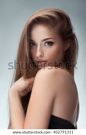 Young brunette lady in black dress posing on grey background