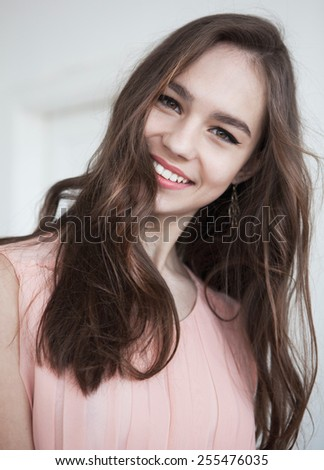 Young brunette lady with a beautiful hair, black liner arrow on gray background - stock photo
