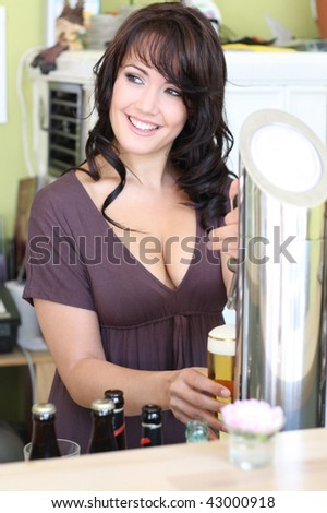 young brunette landlady in a restaurant draws beer at the bar