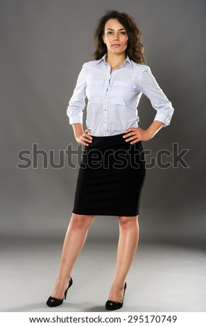 Young brunette latin businesswoman, full length portrait on gray - stock photo