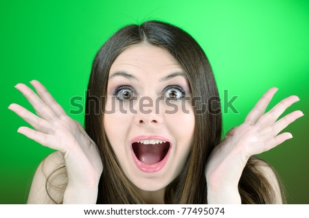 Young brunette looking excited into camera - stock photo