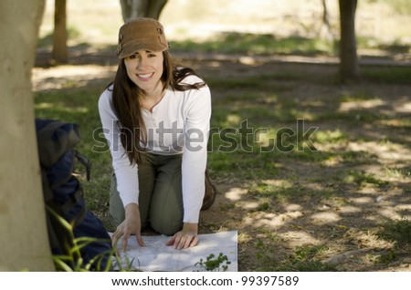 Young brunette looking to a map on the ground and smiling on hiking trip