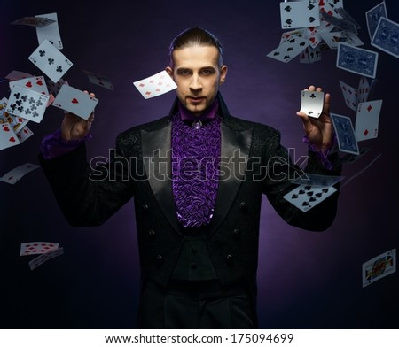 Young brunette magician in stage costume showing card tricks  - stock photo