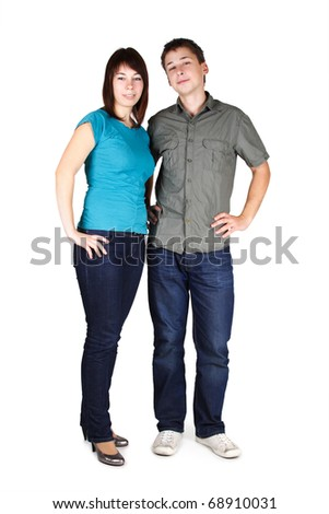 young brunette man and girl in jeans standing and looking at camera, isolated - stock photo