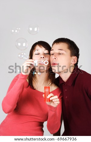 young brunette man and woman in red shirts blowing out soap bubbles - stock photo