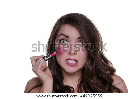 Young brunette model is having a bad make up day.  She has drawn on her cheeks with pink lipstick. - stock photo