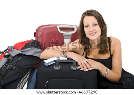 Young brunette posing amidst her luggage, smiling - stock photo