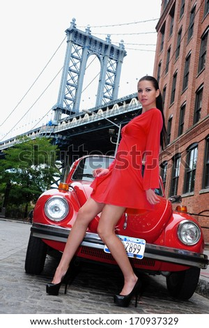 Young brunette posing in red dress in front of vintage car with view to Manhattan bridge at Dumbo area in Brooklyn NY - stock photo