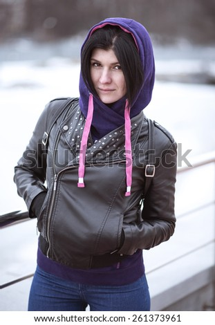 Young brunette posing outdoors in the spring, in a black leather jacket and hood - stock photo
