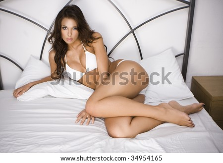 Young brunette sexy glamour woman in white bikini on the bed - stock photo