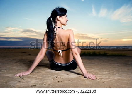 Young brunette sitting on the beach near the sea - stock photo