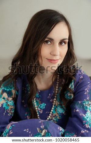 young brunette smiling woman in long violet dress