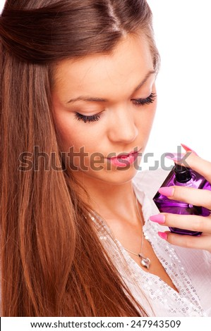 Young brunette spraying perfume on her neck, isolated on white - stock photo