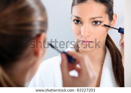 young brunette using eyeliner - stock photo