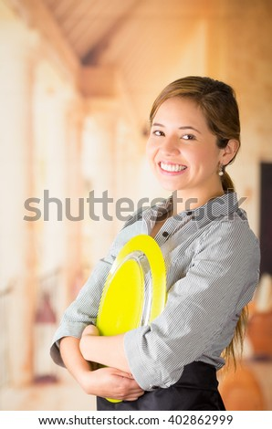 Young brunette waitress holding large yellow plate to chest and smiling at camera, shot from profile angle - stock photo