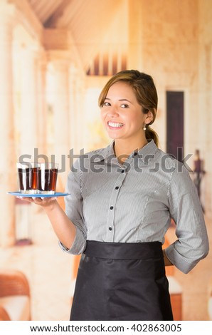 Young brunette waitress wearing uniform with friendly smile, holding up tray containing two glasses of dark liquid using one arm