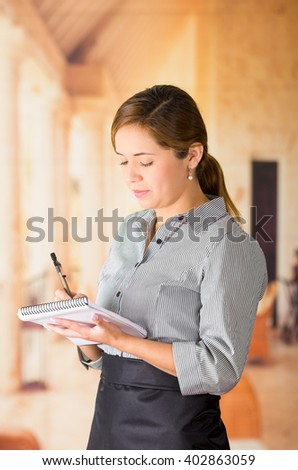 Young brunette waitress with uniform taking order writing on notepad, restaurant background - stock photo