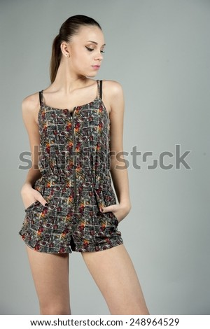 Young brunette wearing a one piece outfit with her hair in a pony tail on a gray background in a studio setting. - stock photo