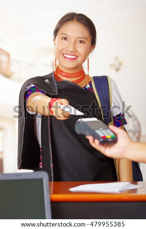 Young brunette wearing traditional native clothes working as hotel receptionist with friendly smile, processing payment using credit card terminal, customers point of view