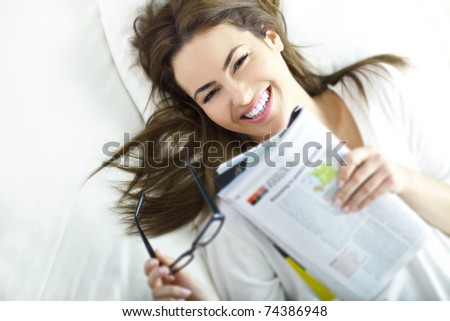 young brunette with magazine - stock photo