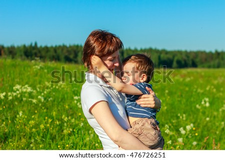 Young brunette with short hair playing with his son in the field. Family fun outdoors.