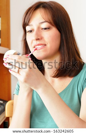 young brunette woman applying lip gloss - stock photo