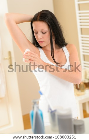 Young brunette woman applying roll-on deodorant under armpit in bathroom - stock photo