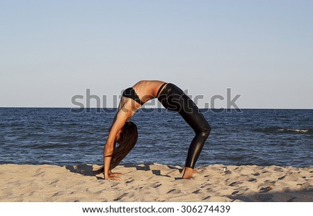 Young brunette woman doing yoga at seaside