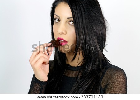 young brunette woman eating chocolate  - stock photo
