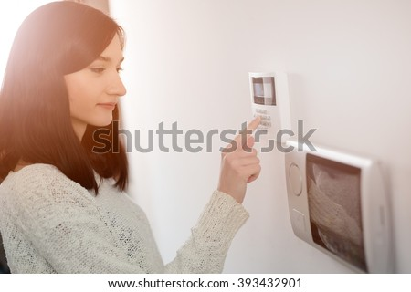 Young brunette woman entering code on keypad of home security alarm. Video intercom next to alarm keypad. - stock photo