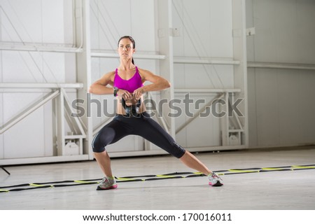 Young brunette woman exercising with a Kettlebell in an indoor urban gym setting. - stock photo