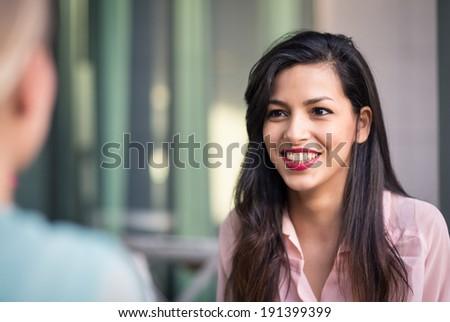 Young brunette woman having fun with friend outdoors. Shallow depth of field.  - stock photo