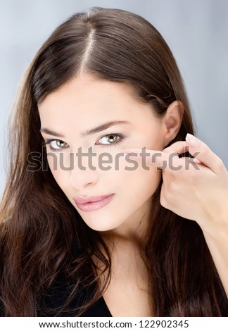 Young brunette woman holding contact lens on finger in front of her eye - stock photo