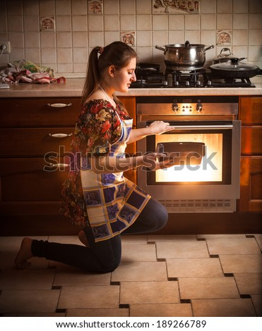 Young brunette woman holding pan with cookies near oven - stock photo