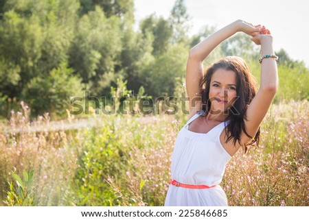 Young brunette woman in a white dress. A girl stands in the middle of pink flowers field on a sunny day. Field, flowers beauty, nature,  - The concept of country vacation. Article about vacation. - stock photo