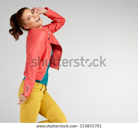 young brunette woman in autumn color isolated on grey - stock photo