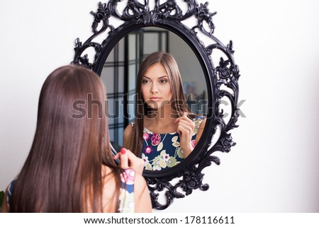 Young brunette woman in beauty salon looking at herself in mirror - stock photo