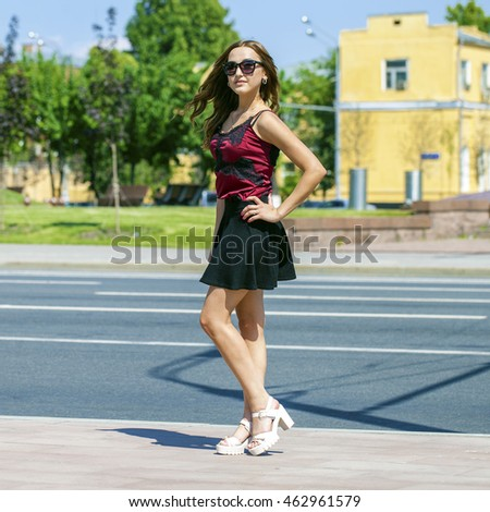 Young brunette woman in black skirt and red blouse, summer street outdoors
