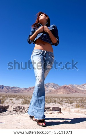 Young brunette woman in blue jeans walking in deserted area - stock photo