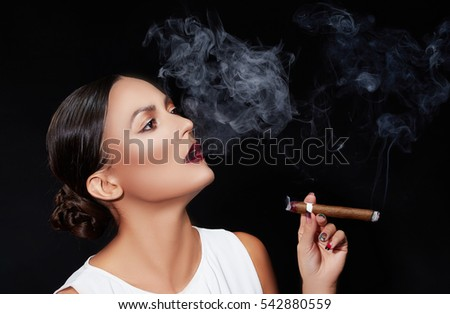 Young brunette woman in business style with cigar on red chair over smoky dark background. Studio portrait.
