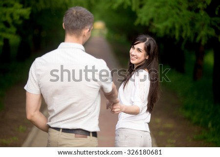Young brunette woman in casual clothes leading by hand her boyfriend, inviting him for a walk in park, playfully looking at him, giggling, follow me concept - stock photo