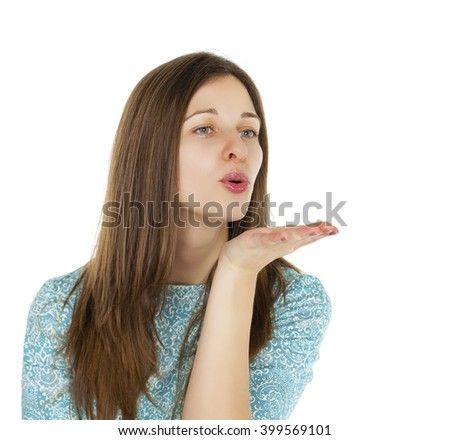 Young brunette woman in dress blowing while sending an air kiss, isolated on white background