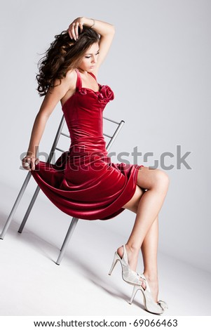 young brunette woman in elegant red dress sit on chair, full body shot, studio shot
