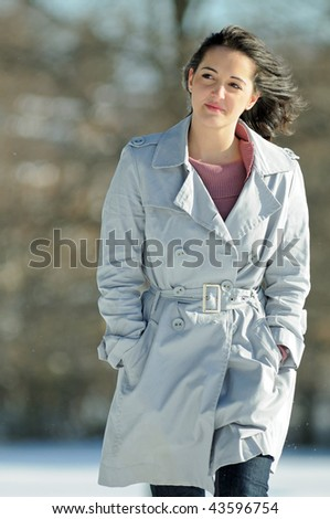 Young brunette woman in gray coat walking in snow - stock photo