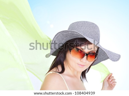 young brunette woman in hat with green wrap over blue background