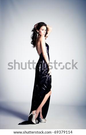 young brunette woman in long elegant dress, standing full body shot, studio shot - stock photo